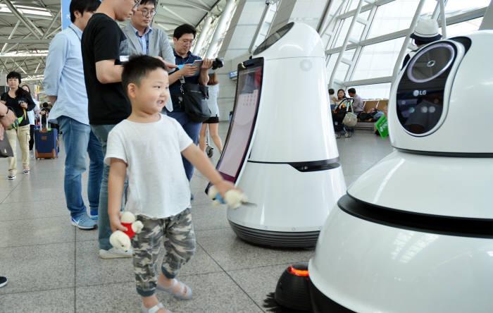 LG전자가 인천국제공항에 공급한 안내 로봇(왼쪽)과 청소로봇.