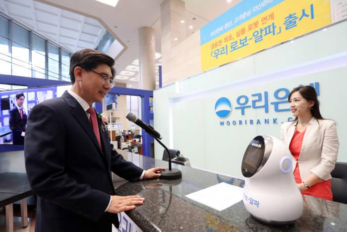 이광구 우리은행장이 '우리 로보-알파'를 탑재한 실물 로봇을 통해 자산관리 상담을 받고 있다.