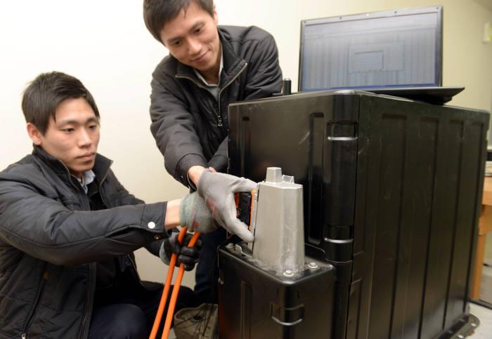 연구원들이 전기차 배터리의 충방전 잔류량을 확인하는 실험을 하고 있다.