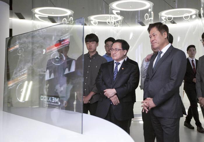 티움 미래관에서 투명 OLED TV를 들여다보며 지구 환경 모니터링 체험을 하고 있는 유영민 과학기술정보통신부장관(앞줄 왼쪽)과 SK텔레콤 박정호 사장(앞줄 오른쪽)의 모습.