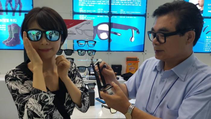 장지문 시선 회장(오른쪽)이 모델이 착용한 블르투스 골전도 스마트 글라스에 대해 설명하고 있다.