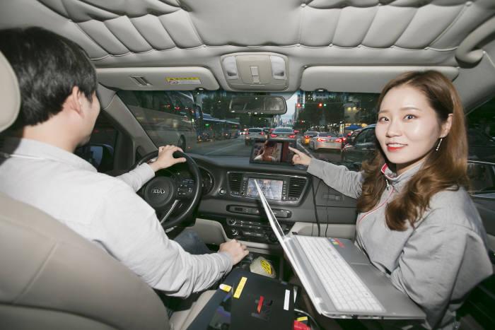 KT의 임직원들이 차량에 구축된 5G-SLT 시스템 연결 상태를 확인하고 있다.