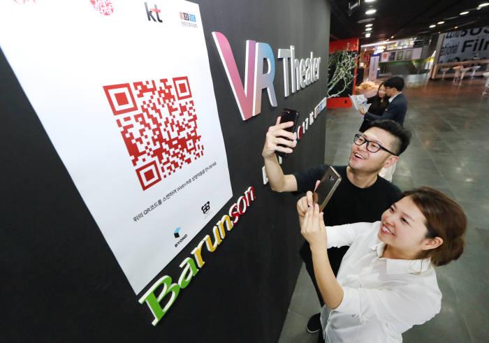 VR영화상영관 참관객이 KT가 제공한 무료 영화 포털 서비스 QR 코드를 스마트폰에 입력하고 있다.
