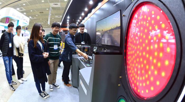 전자·IT의 최첨단기술을 볼 수 있는 '2017 한국전자산업대전'이 17일 서울 삼성동 코엑스에서 나흘간의 일정으로 개최됐다. 참석자들이 이노시뮬레이션의 철도 시뮬레이터를 시연해 보고 있다. 김동욱 기자 gphoto@etnews.com