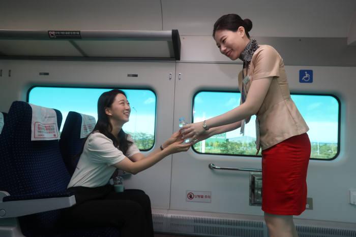 직통열차 승무원이 고객에게 무료 생수를 전달하고 있다.