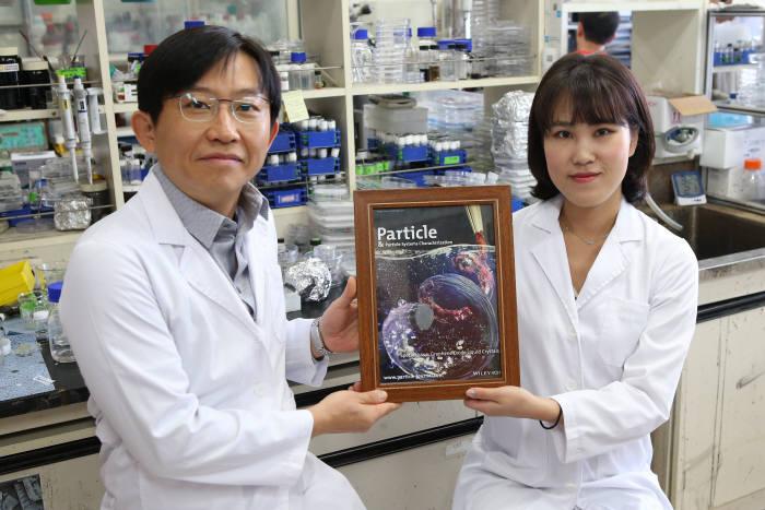 김상욱 KAIST 신소재공학과 교수(왼쪽)이 9월에 나온 파티클 그래핀 산화물 액정 특집호를 들어 보이고 있다.