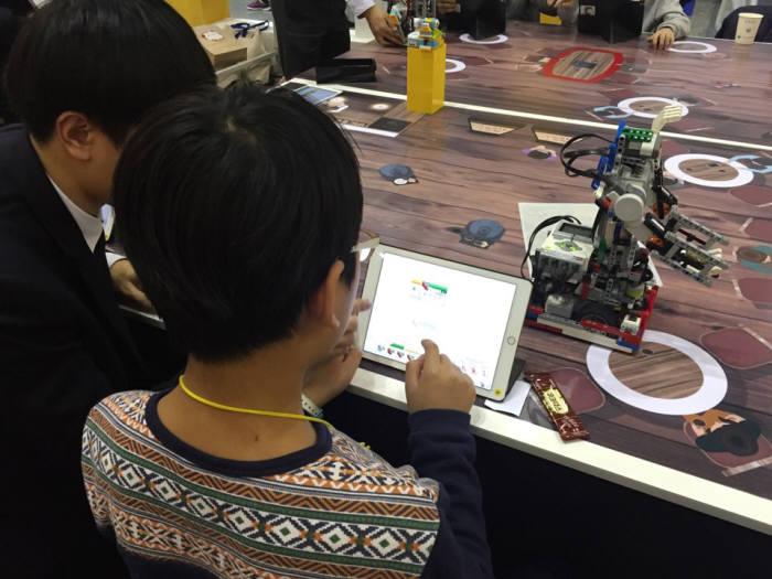SW교육페스티벌에서 초등학생이 고등학생 도움을 받아 로봇을 제어하고 있다.