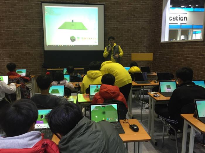 마이크로소프트 직원이 학생들을 대상으로 마인크래프트를 설명하고 있다.