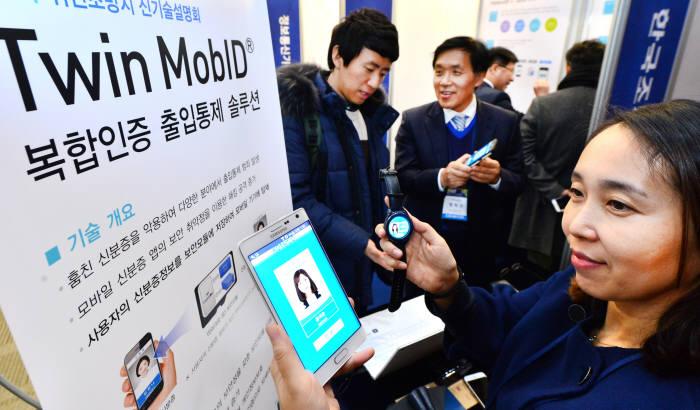 한국조폐공사가 '테크비즈코리아 2016'에서 '복합인증 출입통제 솔루션'을 스마트폰과 스마트워치로 시연하고 있다.