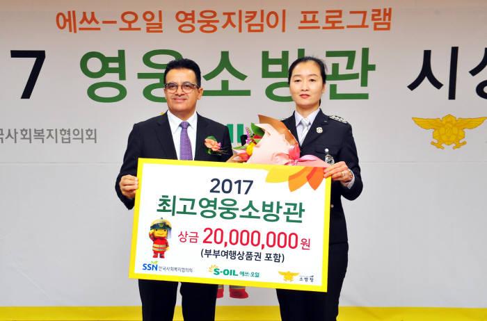 오스만 알 감디 에쓰오일 CEO(왼쪽)가 최고영웅소방관으로 선정된 김미희 소방장에게 상금을 전달하고 기념촬영했다. [자료:에쓰오일]
