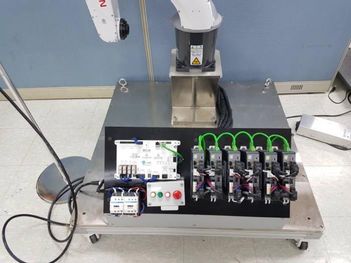 산업용 로봇에 다인큐브가 개발한 세이프티컨트롤러를 적용한 모습. 검은 철판 속 좌상단에 있는 부품이 세이프티컨트롤러.