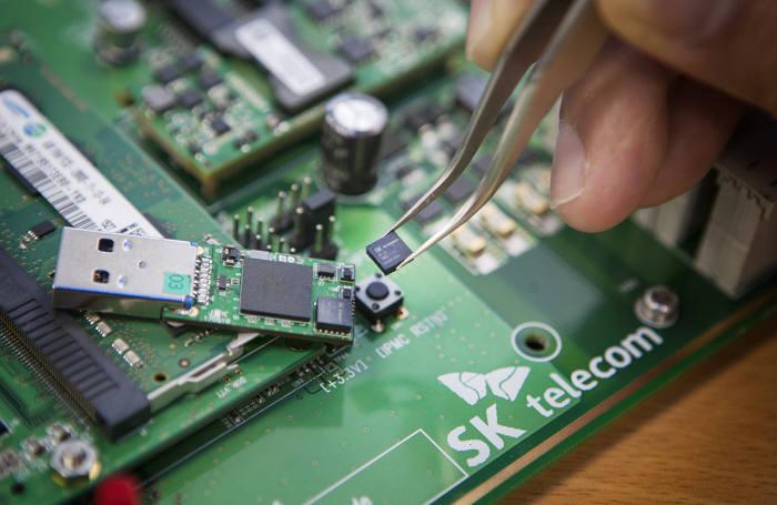 SK텔레콤 퀀텀 테크랩 연구원이 세계 최소 크기(5×5㎜) 양자난수생성 칩을 들고 있는 모습.