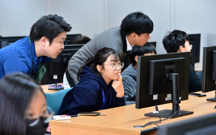 지난해 전자신문이 주최한 드림업 브이월드 공간정보 아카데미에 참여한 학생과 교사가 SW가 설치된 모니터를 바라보고 있다. 전자신문DB