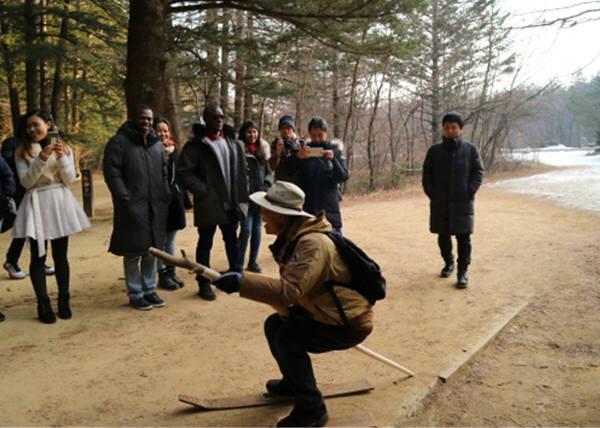 국립공원관리공단 관계자가 오대산국립공원 올림픽 존에서 외국인 관광객들에게 전통 나무 스키 체험에 대해 설명했다. [자료:국립공원관리공단]