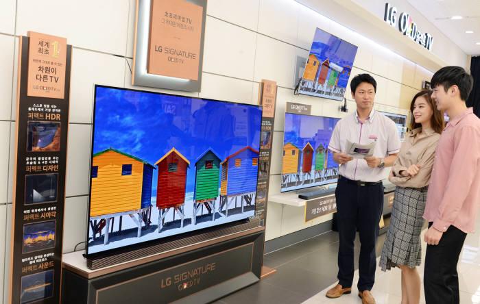LG전자 모델들이 가전 매장에서 'LG 올레드 TV'를 살펴보고 있다.