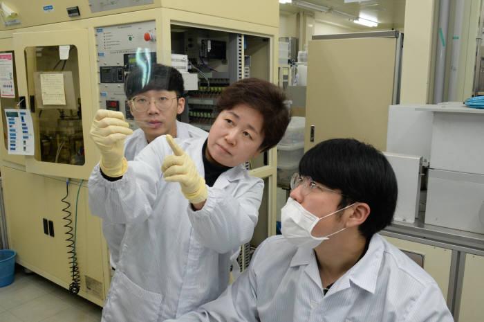 윤선진 박사(사진 중앙)을 비롯한 ETRI 연구진이 고분자 필름 위에 코팅된 이차원 나노시트 필름을 관찰하는 모습