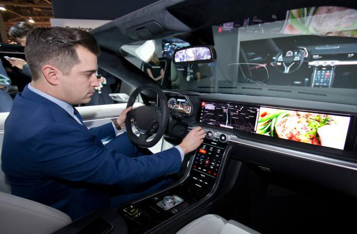 세계 최대 전자 전시회 CES 2018가 개막한 9일(현지시간) 미국 라스베이거스 컨벤션센터(LVCC)의 삼성전자 부스에서 삼성전자 모델이 편리한 운전환경과 인포테인먼트 시스템 제공하는 차량용 '디지털 콕핏'을 시연하고 있다.