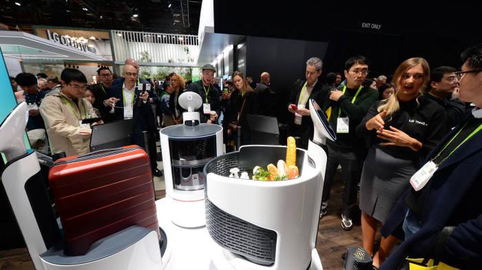 LG전자가 현지시간 9일 미국 라스베이거스에서 개막한 CES 2018에서 로봇 포트폴리오를 총칭하는 브랜드 '클로이(CLOi)'를 공개하고 서빙 로봇, 포터 로봇, 쇼핑 카트 로봇 등 신규 로봇 컨셉 3종을 소개했다. LG전자는 지난해 로봇 사업을 미래 성장동력으로 육성하겠다고 발표한 이후 인공지능, 자율주행 기술 등을 바탕으로 로봇 제품들을 지속 선보이고 있다. 관람객들이 LG전자 부스에서 LG 클로이 로봇 3종을 살펴보고 있다.