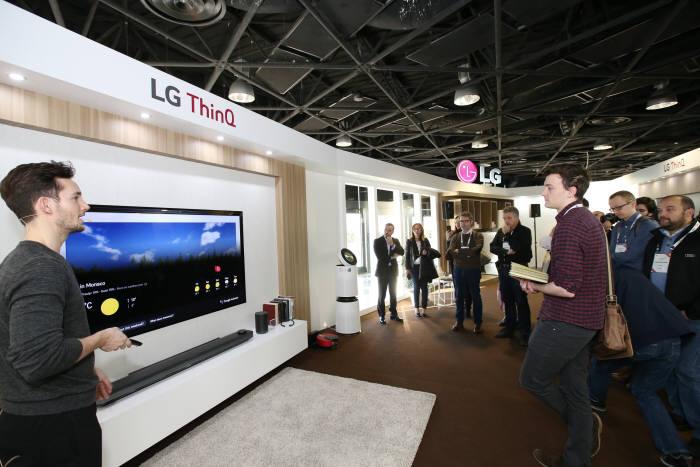 현지 거래선 관계자가 인공지능 기술이 적용된 올레드 TV 음성인식 기능 설명을 듣는 모습.