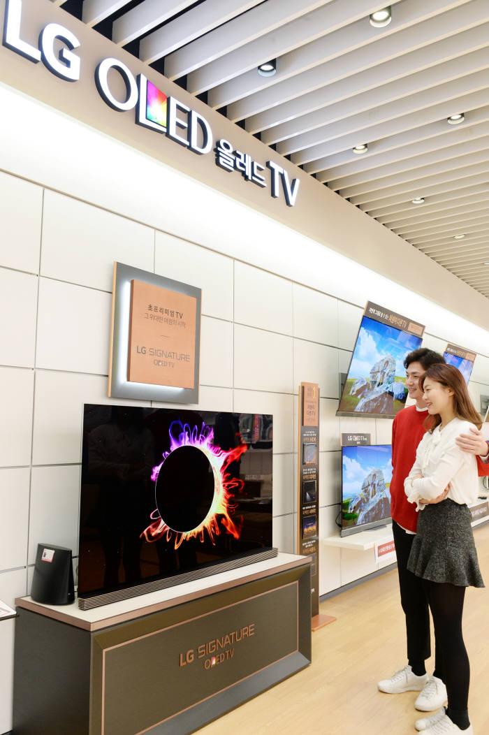 LG전자 모델들이 가전 매장에서 'LG 올레드 TV'를 살펴보고 있다. <자료 LG전자>