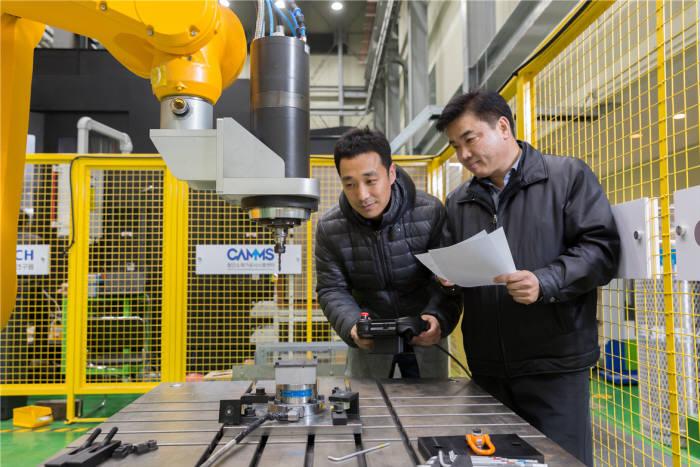 이석우 생기원 박사(왼쪽)와 김태곤 선임연구원이 유연가공시스템에 들어가는 다관절 로봇으로 탄소섬유복합재 드릴링 가공을 시도하고 있다.