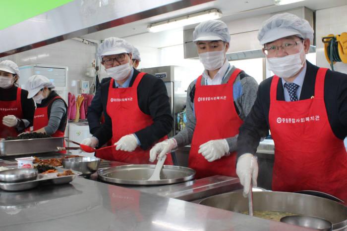 유윤대 농협은행 부행장(오른쪽)과 기업투자금융부문 임직원이 설맞이 무료급식 봉사활동을 펼쳤다.