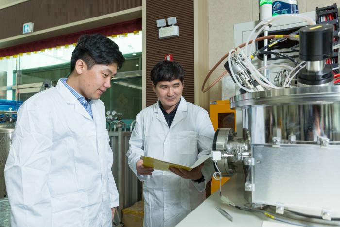 박인욱 수석연구원(사진 오른쪽)이 코팅막 기초연구에 사용되는 장비(멀티스퍼터링 시스템) 가동 모습을 지켜보고 있다.