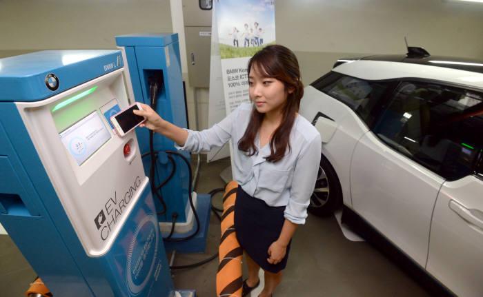 서울 공덕동 이마트에 설치된 충전기에서 한 시민이 전기차를 충전하고 있다. 충전소는 포스코ICT와 BMW 간 협력을 통해 전국 100여개 이마트에 운영 중이다.