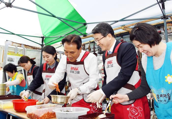BNK금융그룹이 13일 매축지마을(부산 동구 범일동)에서 시민이 운영하는 복지법인 우리마을과 '매축지마을 국수 나눔 잔치'행사를 진행했다. 김지완 BNK금융그룹 회장(왼쪽 네번째)이 국수를 만들고 있다.