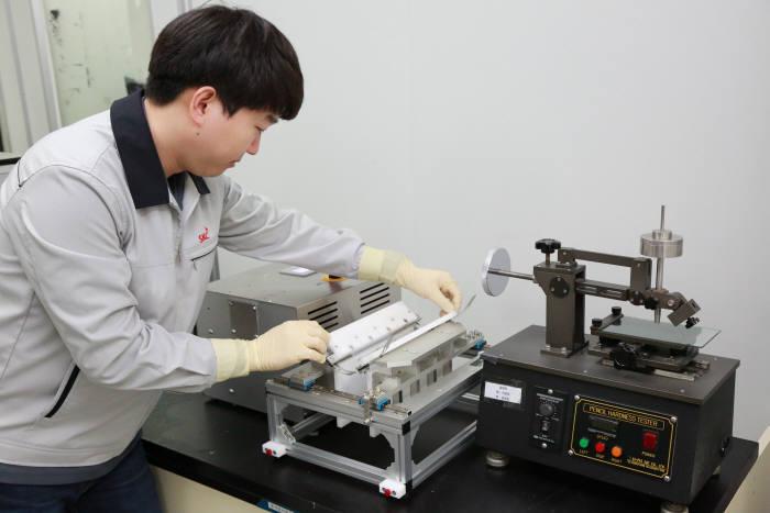 SKC 연구원이 투명PI 필름의 폴딩 실험을 하고 있다(자료: SKC).