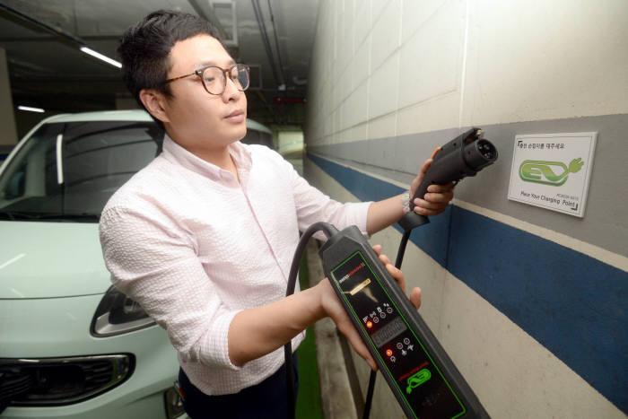 전기차 이용자가 파워큐브의 이동형 충전기로 충전 중인 모습.