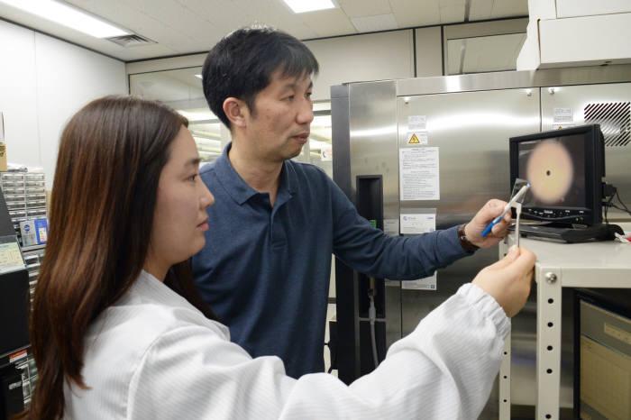 관련 논문 1저자인 김주연 박사(사진 왼쪽)와 황치선 그룹장이 그래핀 기반 투과도 가변 소자의 구조를 확인하고 있다.