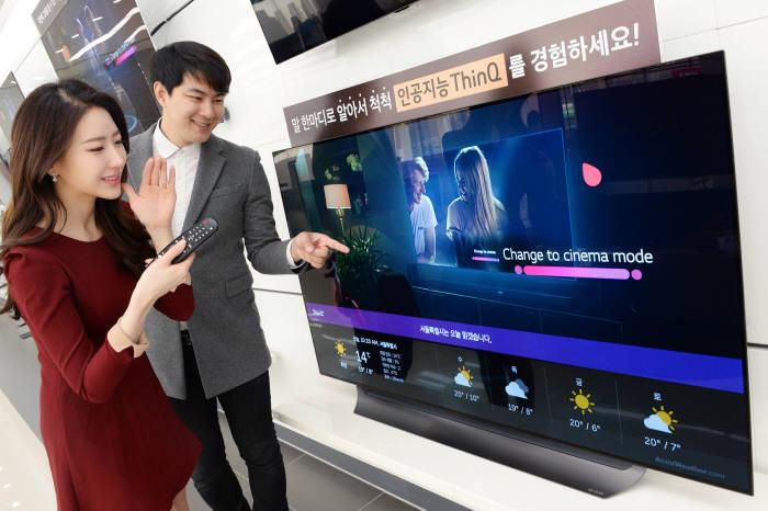 LG전자 모델이 LG 베스트샵 매장에서 LG 올레드 TV를 살펴보고 있다. <자료 LG전자>