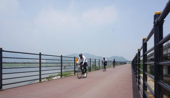 SK케미칼 에코젠이 적용된 목재플라스틱 복합재 자전거 도로 위를 자전거가 달리고 있다. [자료:SK케미칼]