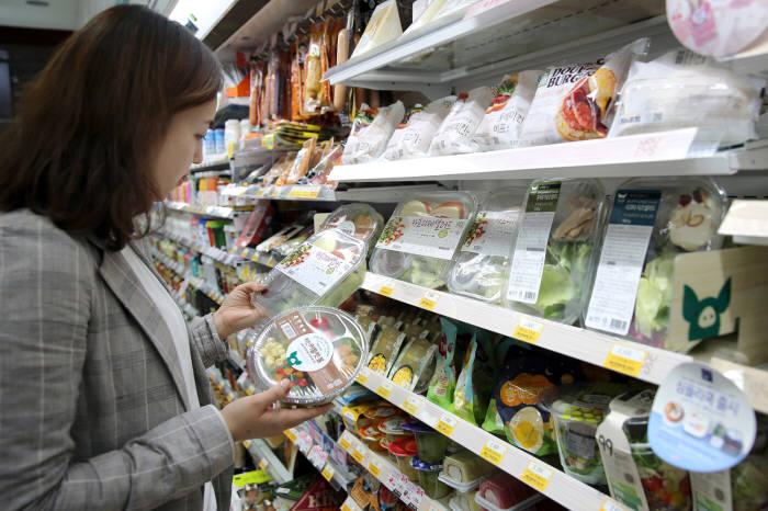 고객이 GS25에서 샐러드를 구매하기 위해 살펴보고 있다.