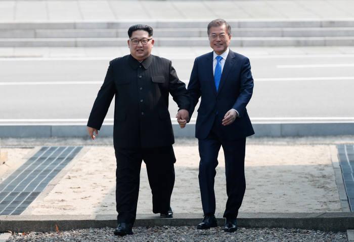 문재인 대통령과 김정은 국무위원장이 27일 군사분계선을 넘고 있다.<한국공동사진기자단>
