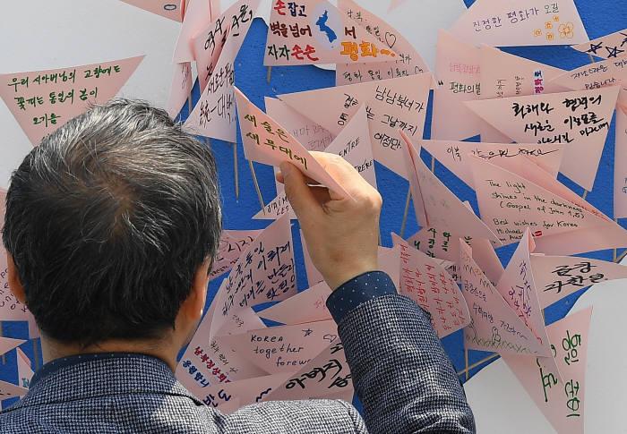남북정상회담 이후 남북 교류 활성화에 대한 기대감이 높다. 한 시민이 서울광장에 마련된 정상회담 이벤트판에 걸린 메시지를 확인하고 있다. 이동근기자 foto@etnews.com
