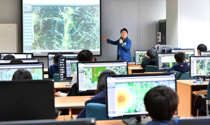 지난해 열린 제2회 드림업 브이월드 공간정보 아카데미에 참여한 학생이 교사 설명을 듣고 있다. 전자신문 DB