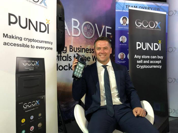 펀디엑스가 GCOX와 협력했다고 9일 밝혔다. 전 영국 프로 축구선수 마이클오웬이 GCOX 전용 펀디엑스 포스(POS) 단말기를 들고 있다.