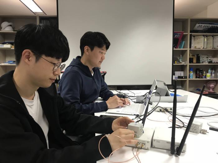 이은규(왼쪽 앞)과 양호준 KAIST 시스템보안연구실 연구팀이 가짜 기지국을 이용한 재난문자 시연을 하고 있다.