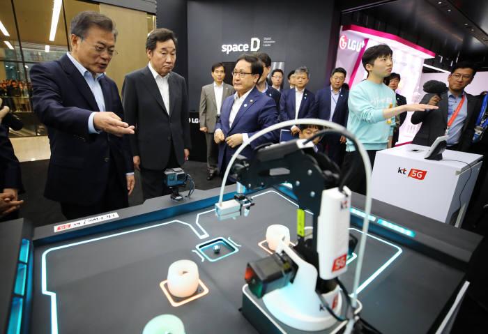 문재인 대통령이 17일 서울 강서구 마곡 R&D 단지에서 열린 '2018 혁신성장 보고대회'에서 이낙연 총리, 유영민 과학기술정보통신부 장관과 함께 KT 5G 기술을 이용한 동작 인식 시연을 지켜보고 있다. <연합뉴스>