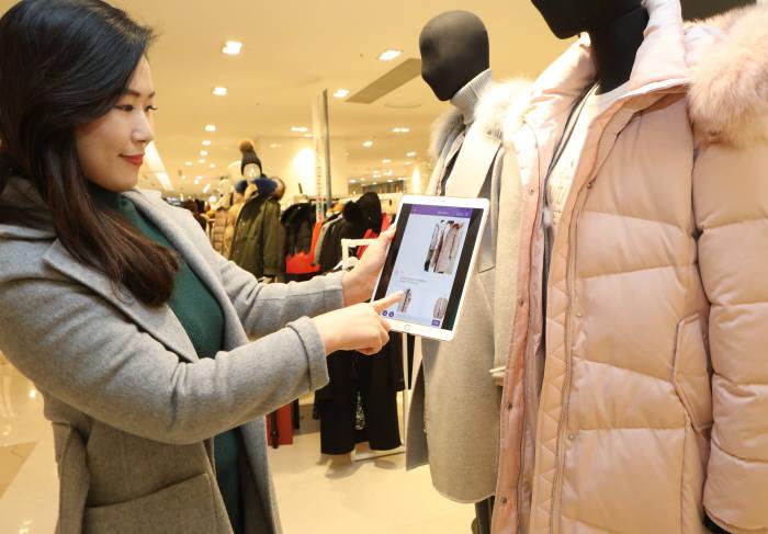 고객이 롯데백화점 본점에서 '이미지 인식(VR)' 서비스를 통해 '로사'에게 상품을 추천 받고 있다.