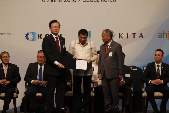 지난 5일 로드리고 두테르테 대통령(가운데)이 배석한 가운데 유정준 SK E&S 사장(왼쪽)과 알폰소 쿠시 필리핀 에너지부 장관이 LOI를 교환했다. <자료:SK E&S>