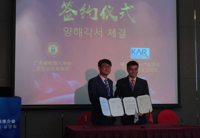 김환근 한국로봇산업협회 부회장(왼쪽)과 임옥동 광동성로봇협회 회장이 양해각서를 체결하고 있다.<사진 한국로봇산업협회>
