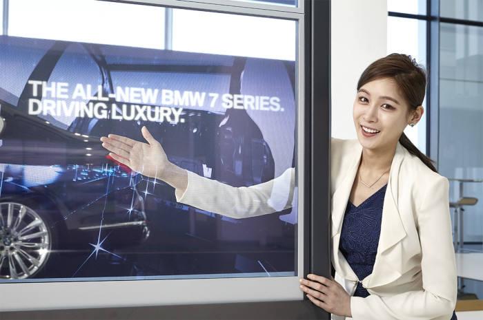 삼성전자 모델이 인천 영종도에 위치한 BMW 드라이빙센터에 새롭게 설치된 투명 OLED 디스플레이 비디오월을 소개하고 있다. <삼성전자 제공>