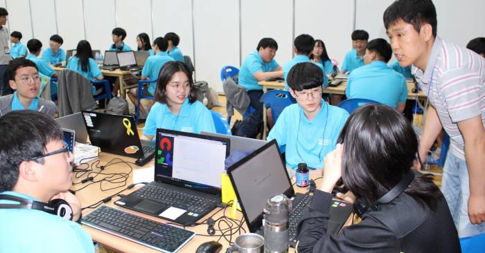 SW해커톤대회에서 멘토(오른쪽)와 학생들이 아이디어 도출을 위해 의견을나누고 있다.