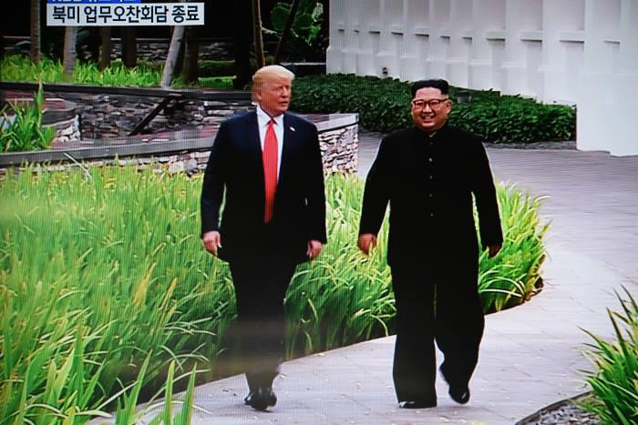 (왼쪽부터)도널드 트럼프 미국 대통령과 김정은 북한 국무위원장이 12일 업무오찬을 마친 뒤 산책을 나섰다.