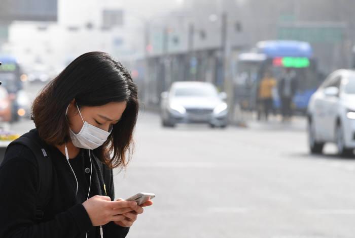 세종대로사거리에서 시민이 마스크를 쓴 채 신호가 바뀌길 기다리고 있다. 전자신문DB