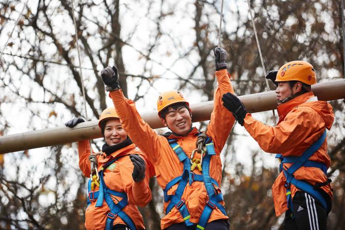 교육생들이 통나무 오르기 챌린지코스를 체험 중이다.