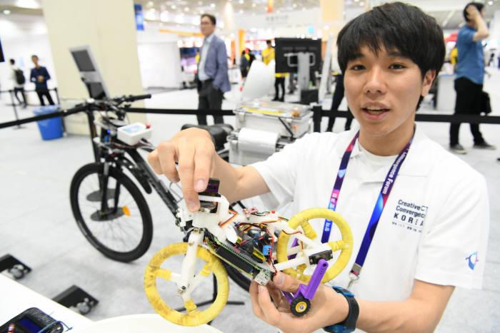 포스텍 창의IT융합공학과 송영운 학생이 좌우 균형을 잡으면서 자율 주행하는 자전거 모형을 들고 원리를 설명하고 있다.